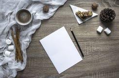 Σε ένα ξύλινο υπόβαθρο ένα φύλλο και μια μάνδρα γράφουν marshmallows και τα γλυκά, μια κούπα με το κακάο βρίσκονται ένας λειωμένο Στοκ Φωτογραφία