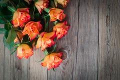 Σε ένα ξύλινο υπόβαθρο υπάρχει η όμορφη ανθοδέσμη των τριαντάφυλλων Στοκ Εικόνα