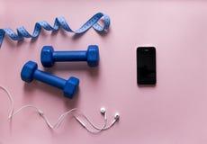 Σε ένα ρόδινο υποβάθρου εγκιβωτισμού τηλεφωνικό smartphone εκατοστόμετρων κορδελλών χρώματος γαντιών μπλε με το λευκό ακουστικών Στοκ Εικόνα