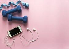 Σε ένα ρόδινο smartphone μουσικής αθλητικών ακουστικών αριθμού μπλε αλτήρων υποβάθρου και εκατοστόμετρων πετάγματος τηλεφωνικό μα Στοκ Εικόνα