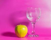 Σε ένα ρόδινο υπόβαθρο η κίτρινη Apple με ένα ποτήρι του νερού Στοκ Φωτογραφία