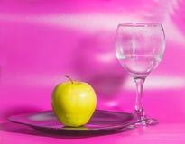 Σε ένα ρόδινο υπόβαθρο στο πιάτο η κίτρινη Apple με ένα γυαλί του W Στοκ φωτογραφία με δικαίωμα ελεύθερης χρήσης