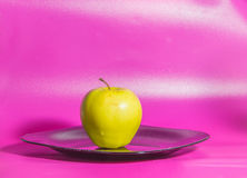 Σε ένα ρόδινο υπόβαθρο στο πιάτο η κίτρινη Apple Στοκ εικόνες με δικαίωμα ελεύθερης χρήσης