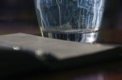 Σε ένα σημειωματάριο υπάρχει ένα ποτήρι του νερού με τις φυσαλίδες με τα αέρια που η λαβή είναι θολωμένη Στοκ φωτογραφίες με δικαίωμα ελεύθερης χρήσης
