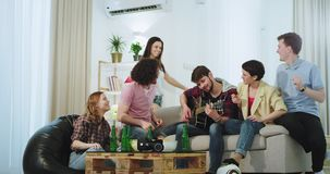 Σε ένα σύγχρονο σπίτι σε μια μεγάλη επιχείρηση οι φίλοι έχουν το χρόνο διασκέδασης που παίζει μαζί σε μια κιθάρα πίνουν την μπύρα απόθεμα βίντεο