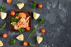 Σε ένα τετραγωνικό πιάτο είναι γαρίδες Κοντά στο πιάτο είναι διεσπαρμένες ντομάτες μαϊντανού, λεμονιών, rucola και κερασιών μαύρο Στοκ Φωτογραφία