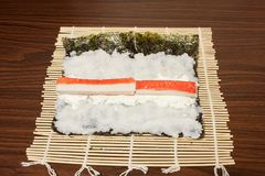 Σε ένα φύλλο Nori χαλιών μπαμπού με το ραβδί ρυζιού, τυριών και καβουριών Στοκ Φωτογραφίες