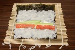 Σε ένα φύλλο Nori χαλιών μπαμπού με το ρύζι, το τυρί, το σολομό και το αγγούρι Στοκ Εικόνες