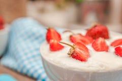 Σε ένα φλυτζάνι του γιαουρτιού και των φρέσκων φραουλών, σε μια μπλε πετσέτα κουταλιών Στοκ φωτογραφία με δικαίωμα ελεύθερης χρήσης