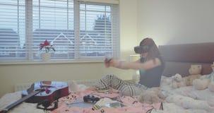 Σε ένα όμορφο κορίτσι εφήβων δωματίων που παίζει σε PlayStation και που χρησιμοποιεί τα γυαλιά εικονικής πραγματικότητας συγχρόνω φιλμ μικρού μήκους