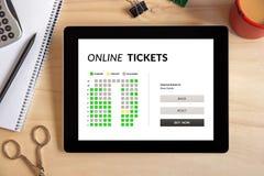 Σε απευθείας σύνδεση έννοια εισιτηρίων στην οθόνη ταμπλετών με τα αντικείμενα γραφείων Στοκ φωτογραφία με δικαίωμα ελεύθερης χρήσης