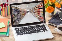 Σε απευθείας σύνδεση αγορές υπεραγορών Υπεραγορά θαμπάδων σε μια οθόνη lap-top, γραφείο γραφείων Στοκ Εικόνες