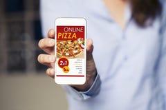 Σε απευθείας σύνδεση αγορές app πιτσών σε μια κινητή τηλεφωνική οθόνη Κλείστε επάνω του χεριού γυναικών κρατώντας τη συσκευή Στοκ Εικόνα