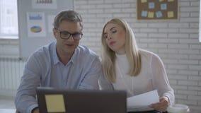 Σε απευθείας σύνδεση διάσκεψη Ένας άνδρας και μια γυναίκα μπροστά από ένα lap-top μιλούν με τους συναδέλφους 4K απόθεμα βίντεο