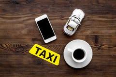 Σε απευθείας σύνδεση διαταγή ένα ταξί που τίθεται με το παιχνίδι αυτοκινήτων, καφές και κινητός στην ξύλινη χλεύη άποψης υποβάθρο Στοκ φωτογραφίες με δικαίωμα ελεύθερης χρήσης