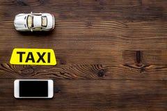 Σε απευθείας σύνδεση διαταγή ένα ταξί που τίθεται με το παιχνίδι αυτοκινήτων και κινητό στην ξύλινη χλεύη άποψης υποβάθρου τοπ επ Στοκ Φωτογραφίες
