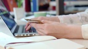 Σε απευθείας σύνδεση λύσεις πληρωμής Χέρια γυναικών που κρατούν την πιστωτική κάρτα και που χρησιμοποιούν το lap-top φιλμ μικρού μήκους
