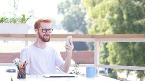 Σε απευθείας σύνδεση τηλεοπτική συνομιλία σε Smartphone, κάθισμα υπαίθριο Στοκ Φωτογραφίες