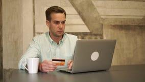 Σε απευθείας σύνδεση τραπεζικές εργασίες Το άτομο κάθεται από τον πίνακα και την πιστωτική κάρτα λαβής απόθεμα βίντεο