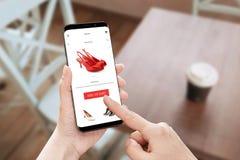 Σε απευθείας σύνδεση app καταστημάτων χρήση στο σύγχρονο κινητό τηλέφωνο με τις στρογγυλές άκρες Στοκ Φωτογραφίες