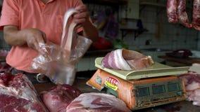 Σε αργή κίνηση ένας προμηθευτής στάβλων που χρησιμοποιεί ένα βάρος για το μεγάλο μπέϊκον χοιρινού κρέατος κομματιών Αγορά απόθεμα βίντεο