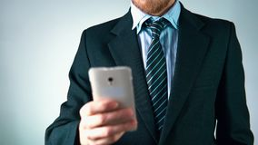 Σε αργή κίνηση, ένα μοντέρνο άτομο σε ένα κοστούμι χρησιμοποιεί ένα κινητό τηλέφωνο φαίνεται κομψός απόθεμα βίντεο
