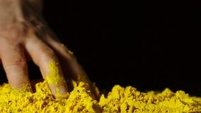 Σε αργή κίνηση: ανθρώπινο χέρι σχετικά με έναν σωρό κίτρινο turmeric σε ένα μαύρο υπόβαθρο απόθεμα βίντεο