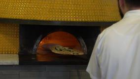 Σε αργή κίνηση αρχιμάγειρας που τοποθετεί την ιταλική πίτσα στον παραδοσιακό ξύλινος-βαλμένο φωτιά φούρνο πετρών απόθεμα βίντεο