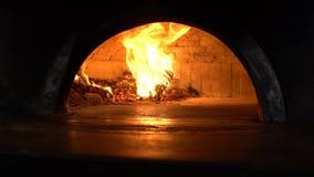 Σε αργή κίνηση αρχιμάγειρας που χρησιμοποιεί το φτυάρι μετάλλων για τα φω'τα μια πυρκαγιά στον ξύλινο φούρνο πετρών απόθεμα βίντεο