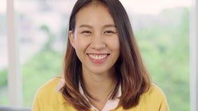Σε αργή κίνηση - ασιατική γυναίκα εφήβων που αισθάνεται το ευτυχές χαμόγελο και που κοιτάζει στη κάμερα ενώ χαλαρώστε στο καθιστι φιλμ μικρού μήκους