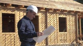 Σε αργή κίνηση βίντεο αρχιτεκτόνων οικοδόμησης έννοιας ο οικοδόμος ατόμων σε ένα κράνος στέκεται σε μια κατασκευή που κρατά ένα σ απόθεμα βίντεο