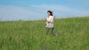 Σε αργή κίνηση βίντεο - γυναίκα που τρέχει σε έναν πράσινο χορτοτάπητα απόθεμα βίντεο