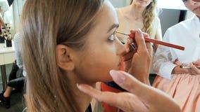 Σε αργή κίνηση βίντεο κινηματογραφήσεων σε πρώτο πλάνο του επαγγελματικού καλλιτέχνη makeup που εφαρμόζει τα καλλυντικά και που π απόθεμα βίντεο