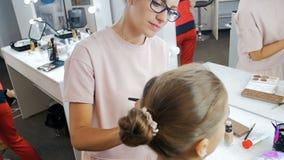 Σε αργή κίνηση βίντεο της νέας όμορφης πρότυπης συνεδρίασης μόδας δίπλα στο μεγάλο καθρέφτη με τους βολβούς ενώ επαγγελματικό mak απόθεμα βίντεο