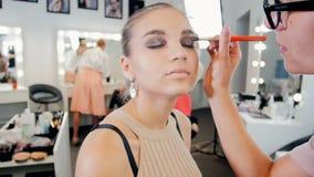 Σε αργή κίνηση βίντεο της νέας όμορφης πρότυπης συνεδρίασης μόδας δίπλα στο μεγάλο καθρέφτη με τους βολβούς ενώ επαγγελματικό mak φιλμ μικρού μήκους