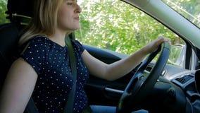 Σε αργή κίνηση βίντεο της όμορφης νέας γυναίκας που οδηγεί ένα αυτοκίνητο και που τραγουδά με το ραδιόφωνο Καλή διάθεση διακινούμ απόθεμα βίντεο