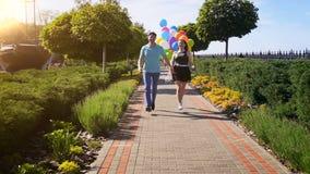 Σε αργή κίνηση βίντεο του ευτυχούς γελώντας ζεύγους που κρατά τη μεγάλη δέσμη των μπαλονιών και που τρέχει στο πάρκο απόθεμα βίντεο