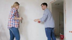 Σε αργή κίνηση βίντεο του νέου ζεύγους που μετρά τους τοίχους στο σπίτι τους κάτω από την ανακαίνιση με τη μέτρηση της ταινίας απόθεμα βίντεο