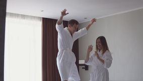 Σε αργή κίνηση βίντεο του νέου ζεύγους που πηδά και που χορεύει στο κρεβάτι μετά από να φθάσει στο ξενοδοχείο απόθεμα βίντεο