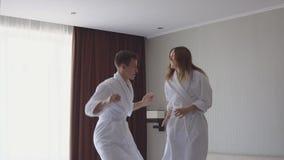 Σε αργή κίνηση βίντεο του νέου ζεύγους που πηδά και που χορεύει στο κρεβάτι μετά από να φθάσει στο ξενοδοχείο φιλμ μικρού μήκους