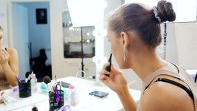 Σε αργή κίνηση βίντεο του όμορφου νέου θηλυκού πρότυπου ισχύοντος makeup κοιτάγματος μόδας στον καθρέφτη στο στούντιο visage απόθεμα βίντεο