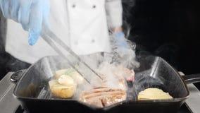 Σε αργή κίνηση βίντεο τροφίμων Αρχιμάγειρας στα γάντια που χρησιμοποιούν τις λαβίδες για τη στροφή του κρέατος στη σχάρα ή τη σχά απόθεμα βίντεο