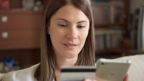 Σε αργή κίνηση γυναίκα στην άσπρη συνεδρίαση μπλουζών στον καναπέ στην αγορά καθιστικών on-line με την πιστωτική κάρτα στο smartp απόθεμα βίντεο
