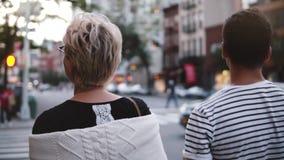 Σε αργή κίνηση δύο ευτυχείς νέοι φίλοι περπατούν μαζί να μιλήσουν, να χαμογελάσουν και να εξερευνήσουν τις οδούς βραδιού της πόλη απόθεμα βίντεο