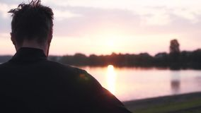Σε αργή κίνηση ελεύθερο ατόμων στην ανατολή Πίσω άποψη του στοχαστικού αρσενικού που απολαμβάνει το ειρηνικό πανόραμα νερού πρωιν απόθεμα βίντεο