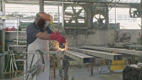 Σε αργή κίνηση ενός εργαζομένου που χρησιμοποιεί το μύλο μετάλλων με τους σπινθήρες που πετούν σε ένα κατάστημα μετάλλων φιλμ μικρού μήκους