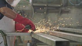 Σε αργή κίνηση ενός εργαζομένου που χρησιμοποιεί το μύλο μετάλλων με τους σπινθήρες που πετούν σε ένα κατάστημα μετάλλων απόθεμα βίντεο