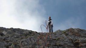 Σε αργή κίνηση ενός ορειβάτη ρίχνει ένα σχοινί στεμένος πάνω από ένα βουνό απόθεμα βίντεο