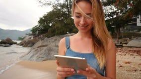 Σε αργή κίνηση επιχειρησιακή γυναίκα που χρησιμοποιεί την ταμπλέτα που περπατά κοντά στο μέγαρο στην παραλία απόθεμα βίντεο