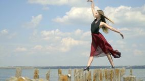 Σε αργή κίνηση λεπτού ξανθού με μακρυμάλλη σε ένα κόκκινο φόρεμα στέκεται στις ξύλινες θέσεις κάτω από τα μπουρίνια του αέρα, απόθεμα βίντεο